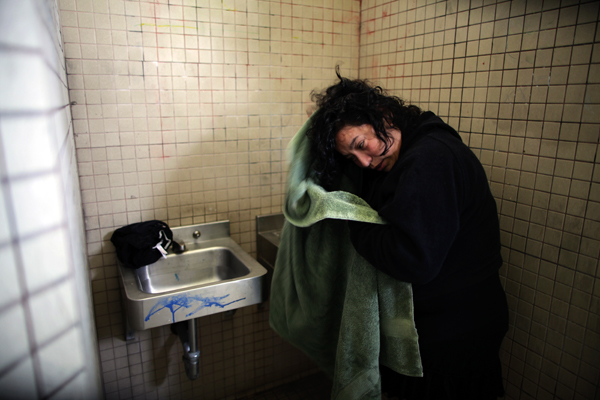 Benita Guzman, 40, washes her hair in the sink of a public restroom after dropping her children at school in Port Hueneme