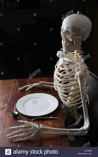skeleton-sitting-at-a-laid-table-with-a-plate-a-knife-a-spoon-and-CXR9A5