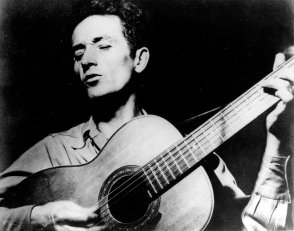 "This is an undated photograph of folk singer Woody Guthrie, singing a song and playing his guitar. Guthrie has written hundreds of songs, celebrating migrant workers, pacifists, and underdogs. Two of his well-known songs are ""So Long, It's Been Good to Know You,"" and ""This Land is Your Land."" (AP Photo)"